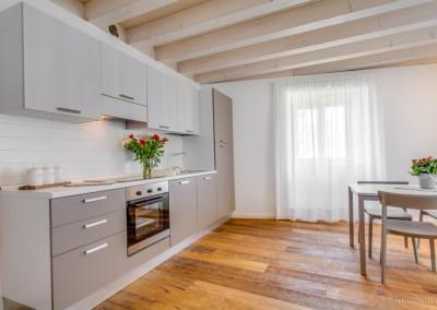 Cucina con forno, frigorifero, piano ad induzione e pentolame professionale.